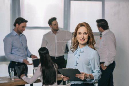 selective focus of smiling businesswoman and colleagues behind at workplace in office