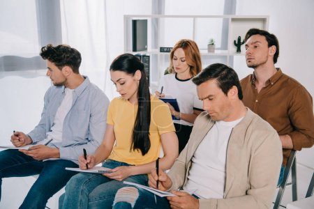 focused businessmen and businesswomen in casual clothing making notes in notebooks on business training in office