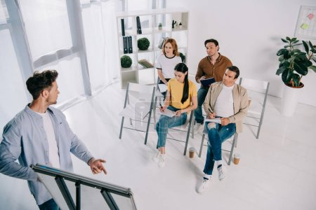 partial view of business people listening to mentor during business training in office
