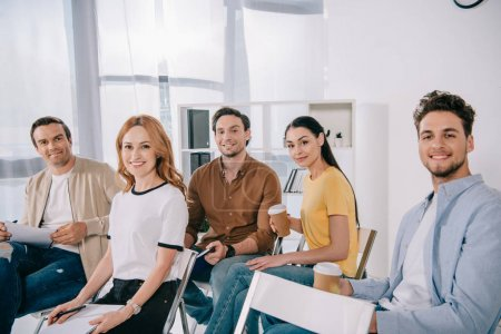 smiling business people in casual clothing having business training in office