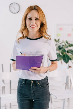 portrait of smiling businesswoman in casual clothing with notebook in hands, business training concept