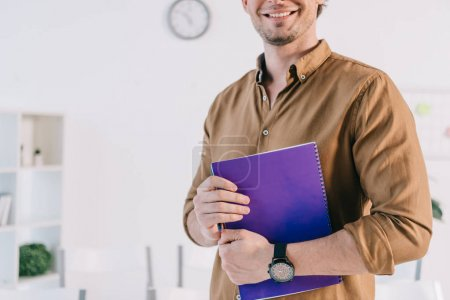 cropped shot of smiling businessman in casual clothing with notebook n office, business training concept