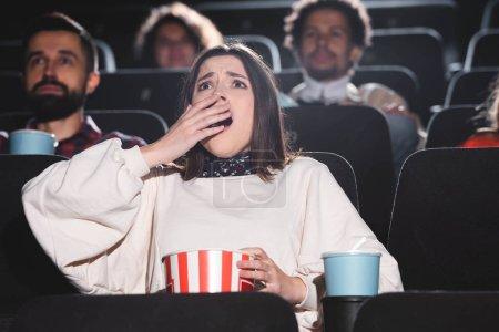 Photo pour Focalisation sélective de la femme choquée tenant du maïs soufflé et regardant des films au cinéma - image libre de droit