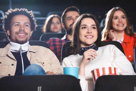 Photo pour Focalisation sélective d'amis multiethniques souriant et regardant des films au cinéma - image libre de droit