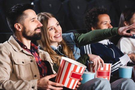 Photo pour Focalisation sélective de la femme pointant du doigt et regardant le film avec des amis multiculturels au cinéma - image libre de droit