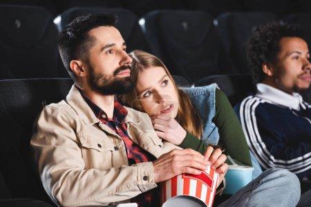 Photo pour Foyer sélectif de la femme effrayée couchée sur l'épaule et regarder un film avec des amis multiculturels au cinéma - image libre de droit