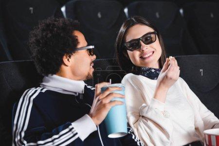 Photo pour Amis multiculturels dans des lunettes 3D se regardant et souriant au cinéma - image libre de droit