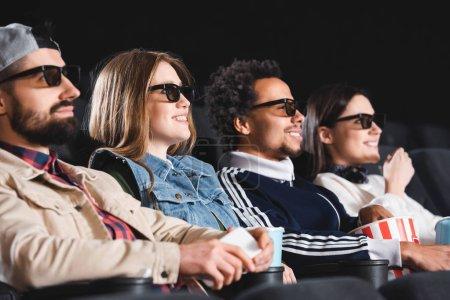 Photo pour Des amis multiculturels dans des lunettes 3D souriant et regardant des films au cinéma - image libre de droit