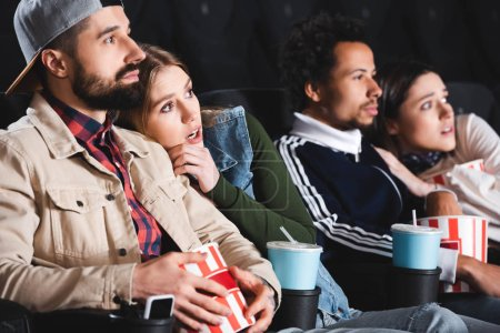 selective focus of scared multicultural friends watching movie in cinema