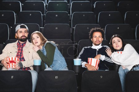 Photo pour Des amis multiculturels effrayés avec du pop-corn regardant des films au cinéma - image libre de droit