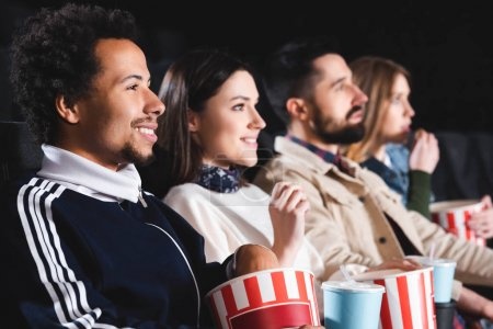 Photo for Selective focus of african american man watching movie with friends in cinema - Royalty Free Image