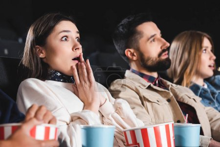 Photo for Selective focus of shocked woman watching movie with friends in cinema - Royalty Free Image