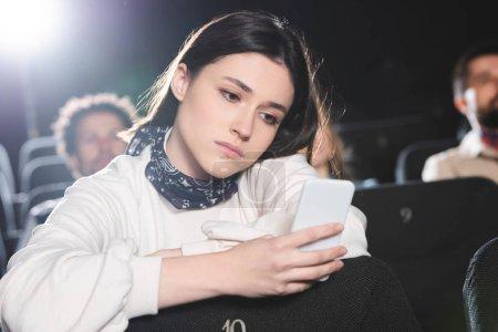 Photo pour Selective focus of sad woman using smartphone in cinema - image libre de droit