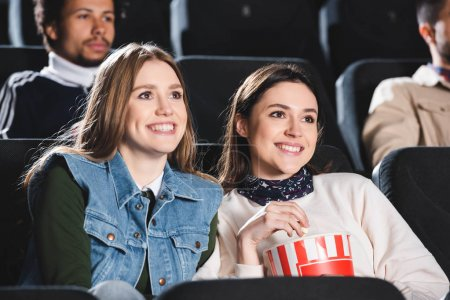Photo for Selective focus of smiling friends watching movie in cinema - Royalty Free Image