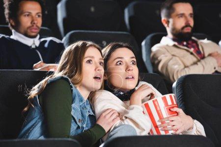 Photo pour Focalisation sélective des amis effrayés avec le pop-corn regarder des films au cinéma - image libre de droit