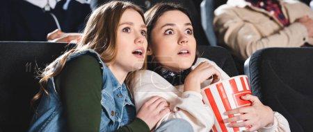 Photo pour Photo panoramique d'amis effrayés avec pop-corn regardant un film au cinéma - image libre de droit