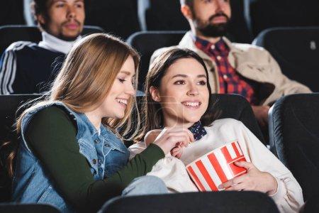 Photo pour Focalisation sélective des amis souriants avec pop-corn regarder des films au cinéma - image libre de droit