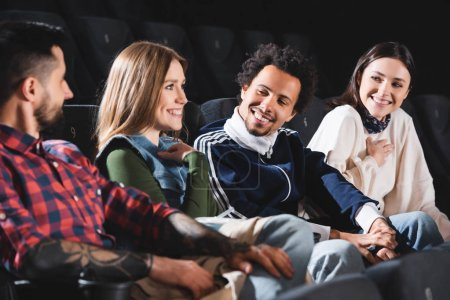 Photo for Selective focus of multicultural friends smiling and talking in cinema - Royalty Free Image