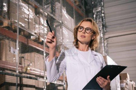 Photo pour Attrayant magasinier tenant presse-papiers, regardant loin et pointant avec stylo dans l'entrepôt - image libre de droit