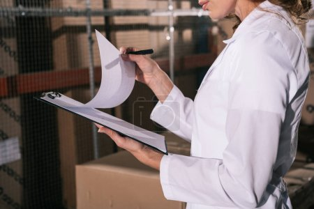 Photo pour Cropped view of storekeeper holding clipboard with documents in warehouse - image libre de droit