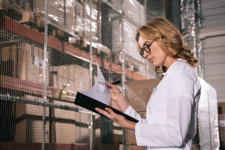 Photo pour Concentrated storekeeper looking at papers on clipboard in warehouse - image libre de droit