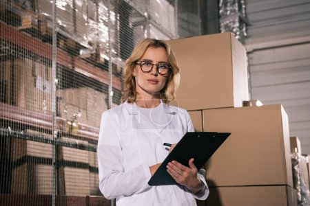 Photo for Serious storekeeper looking at camera while writing on clipboard in warehouse - Royalty Free Image