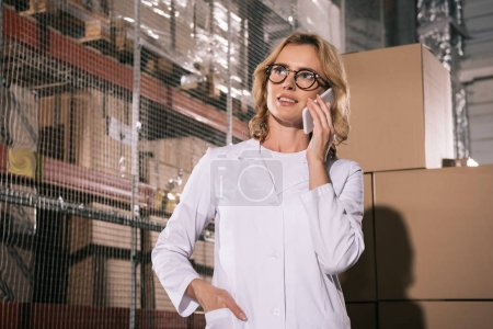 Photo for Smiling storekeeper talking on smartphone while standing with hand in pocket in warehouse - Royalty Free Image