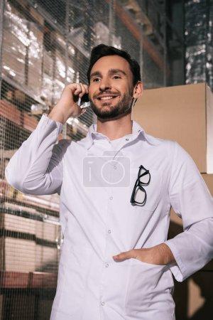 Photo pour Un magasinier souriant en train de parler de smartpone alors qu'il est debout avec la main dans la poche dans l'entrepôt - image libre de droit