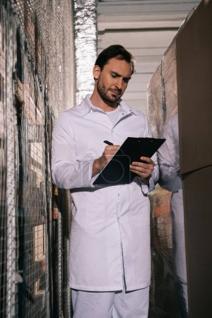 Photo for Focused storekeeper in white coat writing on clipboard in warehouse - Royalty Free Image