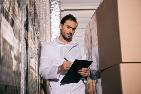 Photo for Concentrated storekeeper in white coat writing on clipboard in warehouse - Royalty Free Image