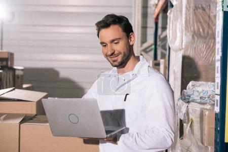 Photo pour Un magasinier souriant qui utilise un ordinateur portatif tout en se tenant debout près de boîtes de carton dans un entrepôt - image libre de droit