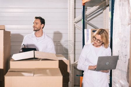 Photo pour Attractive storekeeper using laptop near handsome colleague writing on clipboard in warehouse - image libre de droit