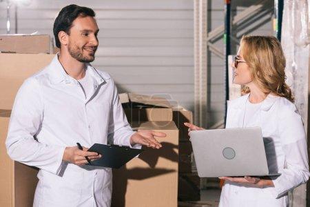 Photo pour Beau magasinier parlant à un collègue qui tient un ordinateur portatif en entrepôt - image libre de droit