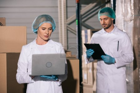 Photo pour Attrayant magasinier en utilisant un ordinateur portable près de collègue regardant presse-papiers dans l'entrepôt - image libre de droit