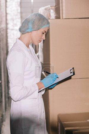 Photo pour Magasinier spécialisé en coiffure écrite sur une planche à reliure alors qu'il se tient près de boîtes à carton dans l'entrepôt - image libre de droit