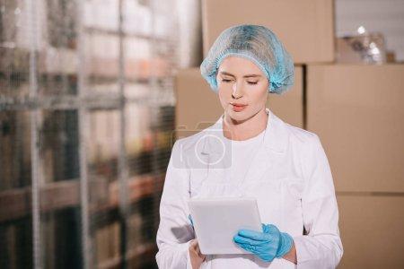 Photo pour Magasinier concentré dans hairnet en utilisant la tablette numérique dans l'entrepôt - image libre de droit