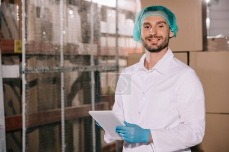 Photo pour Cheerful storekeeper in white coat and hairnet holding digital tablet and looking at camera - image libre de droit