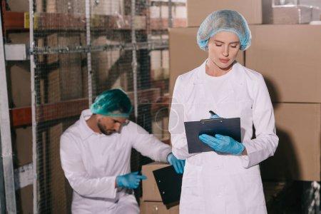 Photo pour Un magasinier attirant écrit sur le presse-papiers près d'un collègue inspectant une boîte en carton - image libre de droit