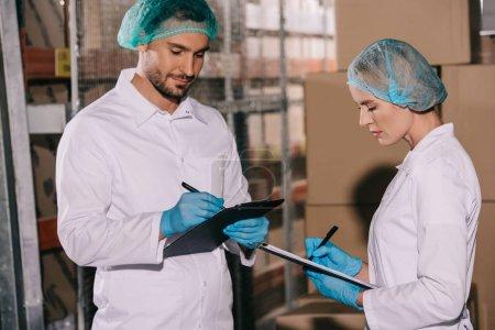 Photo pour Deux magasiniers en manteaux blancs et en filets de coiffure écrivant sur des planches à pince dans l'entrepôt - image libre de droit