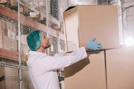 Photo pour Magasinier vêtu d'un manteau blanc et d'un filet à cheveux boîte de carton dans l'entrepôt - image libre de droit