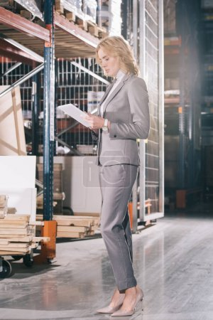 Photo pour Focused businesswoman using laptop while standing near construction materials in warehouse - image libre de droit