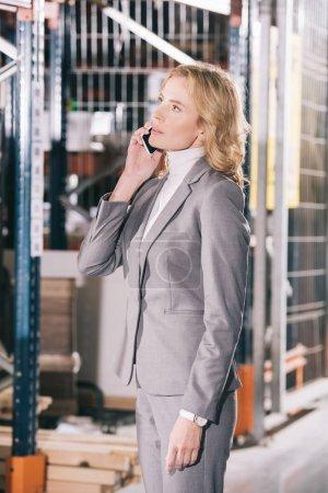 Photo pour Une femme d'affaires sérieuse parle sur un téléphone intelligent et regarde dehors dans un entrepôt - image libre de droit