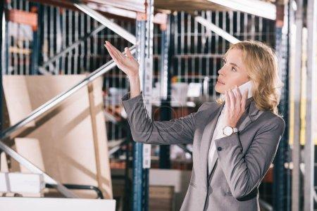 Photo pour Femme d'affaires sérieuse parlant sur smartphone, détournant les yeux et pointant la main dans l'entrepôt - image libre de droit