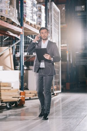 Photo for Serious businessman talking on smartphone and holding clipboard in warehouse - Royalty Free Image