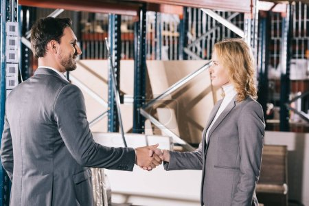 smiling businessman and businesswoman shaking hands in warehouse