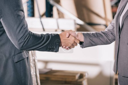 cropped view of businesspeople shaking hands in warehouse