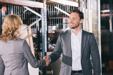 Photo pour Homme d'affaires souriant serrant la main d'une femme d'affaires dans un entrepôt - image libre de droit
