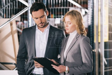 Photo pour Concentrated businessman and businesswoman looking at clipboard in warehouse - image libre de droit