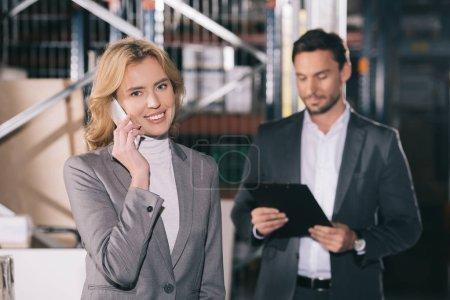 Photo pour Foyer sélectif de femme d'affaires gaie regardant la caméra tout en parlant sur smartphone près de l'homme d'affaires - image libre de droit