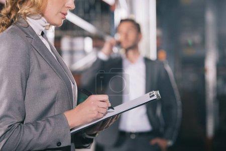 Foto de Enfoque selectivo de las empresarias que escriben en el portapapapeles cerca de los hombres de negocios hablando en teléfono inteligente en el almacén. - Imagen libre de derechos